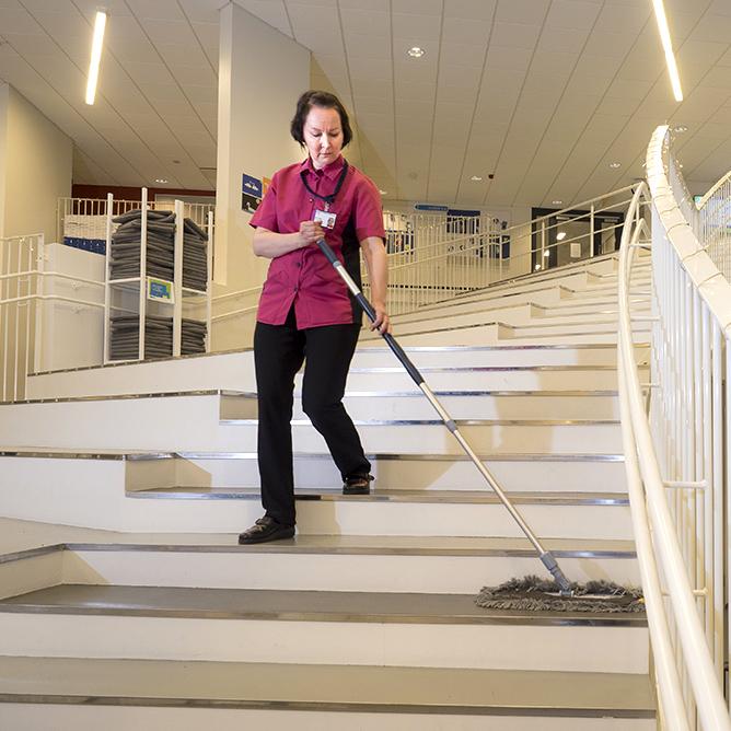 Laitoshuoltaja puhdistaa portaita Jalossa levykehysmopilla
