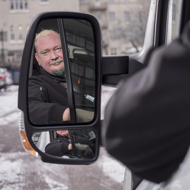 Autonkuljettaja katsoo sivupeilistä taakseen. Kuvasta linkki töihin meille sivulle.