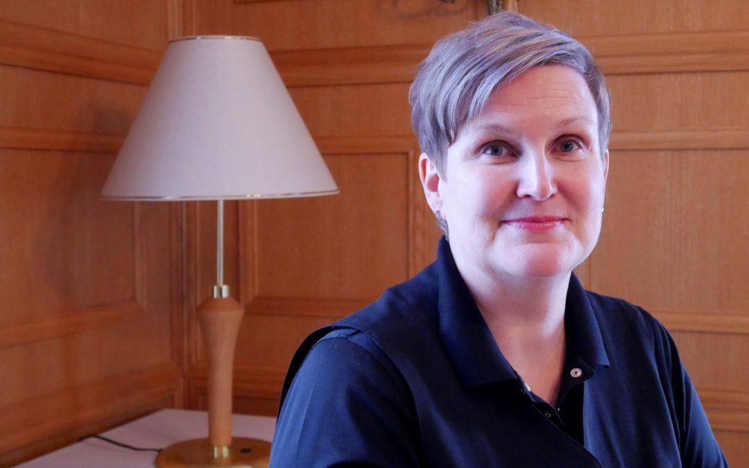 Kuvassa Katri Messilästä istuu tuolilla ja hymyilee kameralle